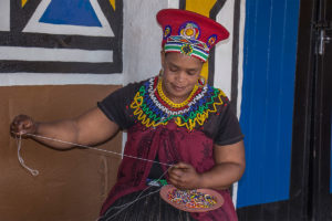 A-Zulu-lady-weaving-in-one-of-the-tourists-attraction-Restaurants-in-South-Africa-named-Lesedi-Village